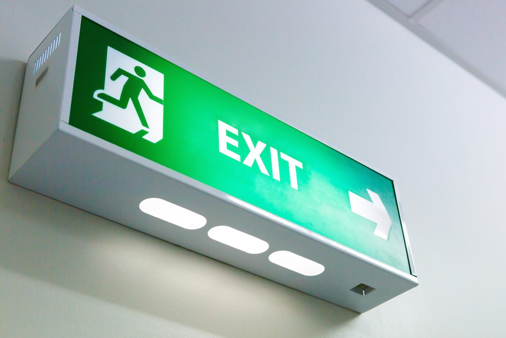 The Fire exit sign in big factory